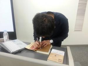 サインを書いてる中村あきら