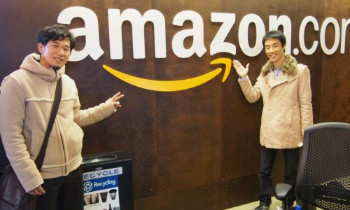 Amazon(アマゾン)のロゴの前で