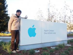 Apple(アップル)本社のロゴの前で