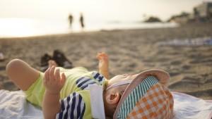 海辺で寝転がる赤ん坊